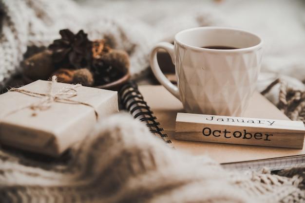 Maglioni e tazza di tè con taccuino, candela e vestiti a maglia