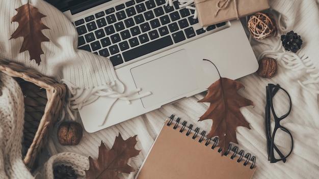 Maglioni e tazza di tè con notebook, laptop e maglieria