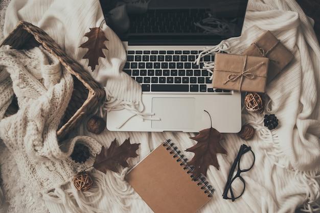 Maglioni e tazza di tè con notebook, laptop e vestiti a maglia