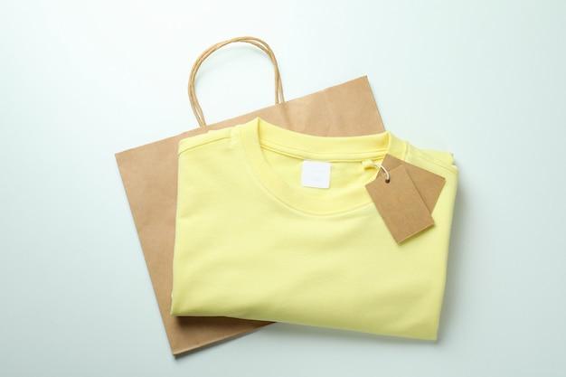 Felpa con etichette e borsa su superficie bianca