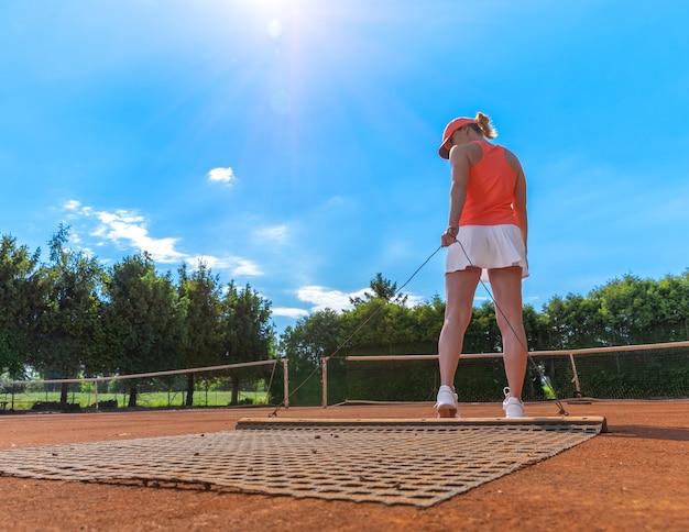 Spazzare l'argilla arancione su un campo da tennis all'aperto. giovane donna