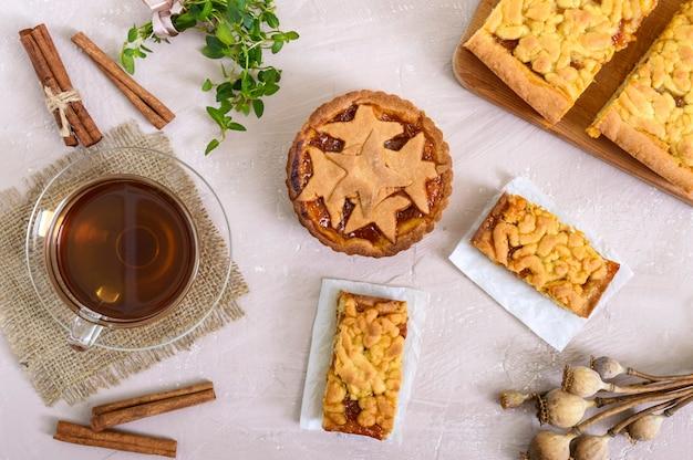 Torta di albicocche dolce - tortino di pasta sfoglia ripieno di marmellata e una tazza di tè alla cannella. vista dall'alto.