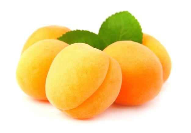 Frutti di albicocche dolci con foglie su bianco