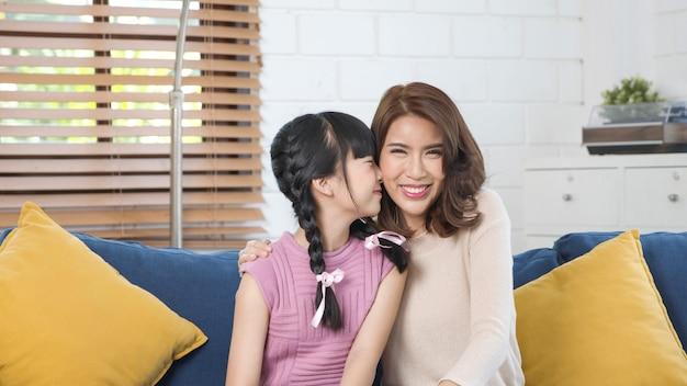 Dolce bambina asiatica sta abbracciando e baciando la sua bella giovane madre in guancia mentre era seduto sul divano di casa.