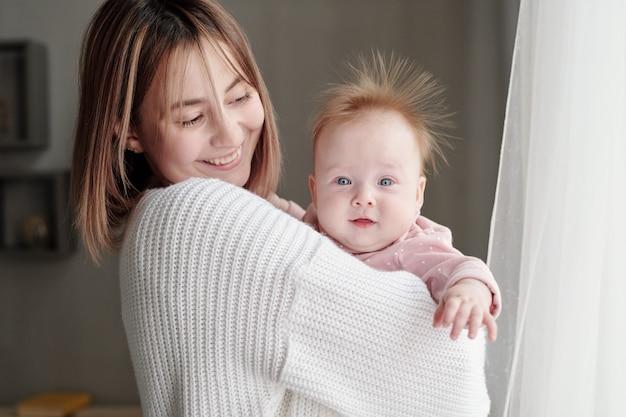 Dolce neonata sulle mani di sua madre che guarda l'obbiettivo