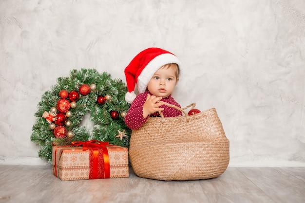 Il dolce bambino santa si siede in un cesto di vimini con una confezione regalo