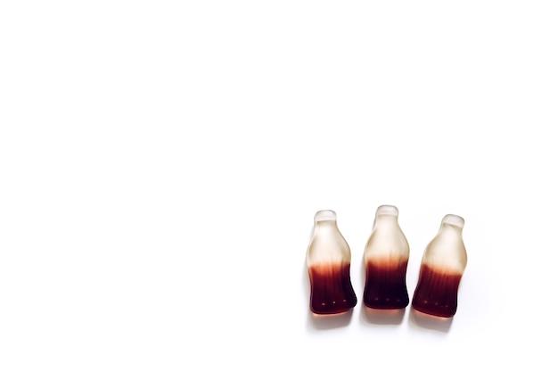 Sfondo dolce di tre caramelle gommose al gusto di cola di gelatina a forma di bottiglia
