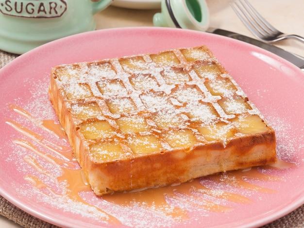 Cialda belga dolce con miele su un piatto rosa