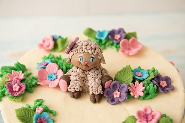 Dolce torta di compleanno decorata con fiori e zucchero di pecora Foto Premium