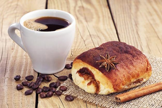 Panino dolce con cannella e tazza di caffè caldo