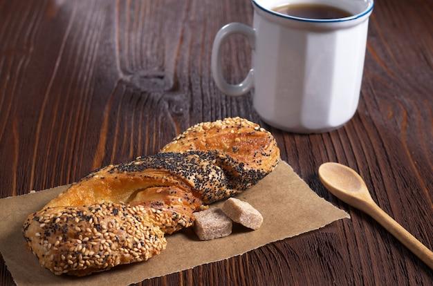 Panino dolce con semi di lino e papavero e tazza di tè sul tavolo