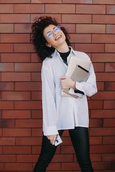 Dolce donna d'affari con i capelli ricci è in posa felicemente su un muro di pietra mentre tiene il suo computer