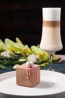 Torta dolce e caffè latte su uno sfondo nero