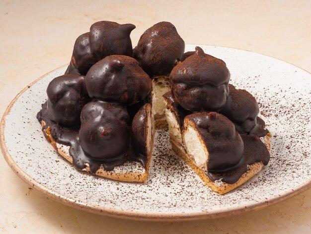 Torta dolce un croquembouche di profiteroles con panna e un filo di cioccolato