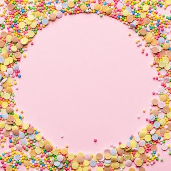 Ingrediente per pasticceria dolce. confettini di zucchero a forma di cerchio. cornice rotonda con topping di pasta. design vuoto al centro. isolato su sfondo rosa. concetto di vacanza e compleanno.