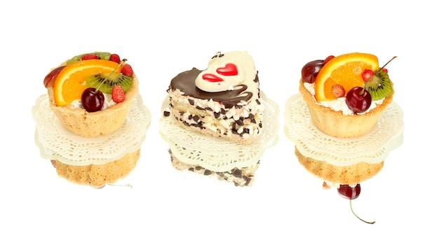 Torte dolci con frutta e cioccolato su bianco