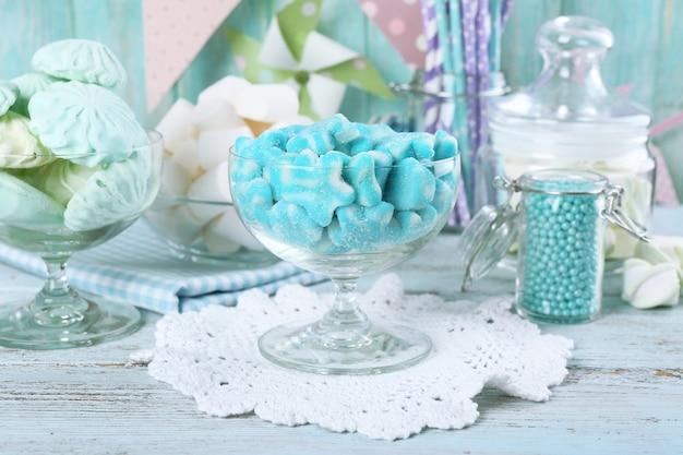 Caramelle dolci in cristalleria sulla tavola di legno, primo piano