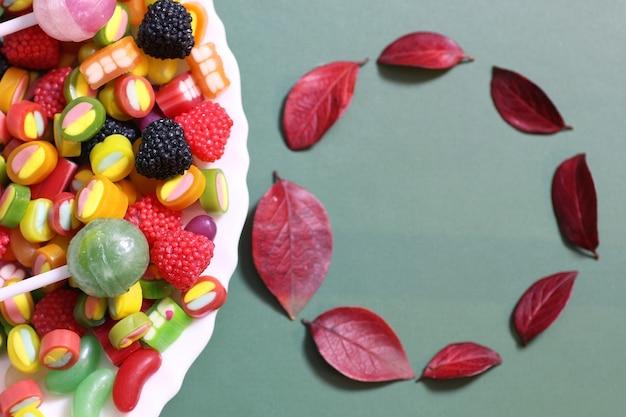Fagiolo di gelatina di caramelle dolci multi colore su uno sfondo verde piatto