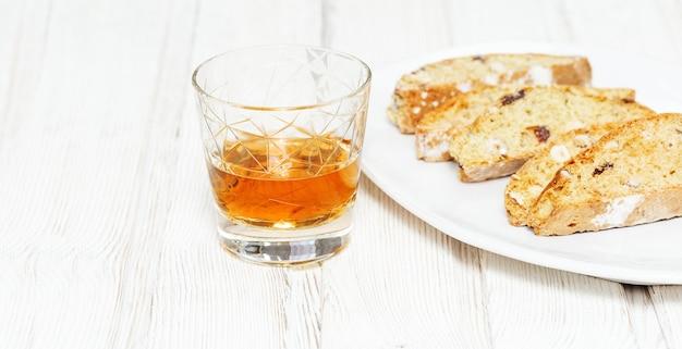 Cantuccini dolci e vino. biscotti italiani fatti in casa di biscotti sulla tavola di legno. Foto Premium