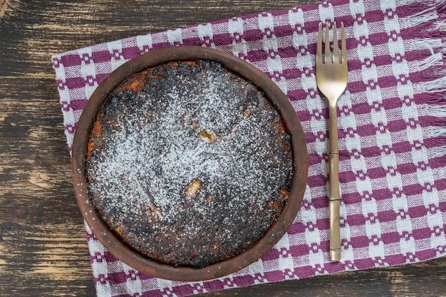 Casseruola dolce con una crosta bruciata sulla tavola di legno. ciotola in ceramica con casseruola di ricotta al forno, primo piano, vista dall'alto