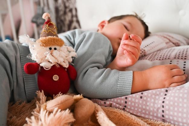 Dolce ragazzo caucasico toodler che dorme nel suo letto con uno gnomo giocattolo