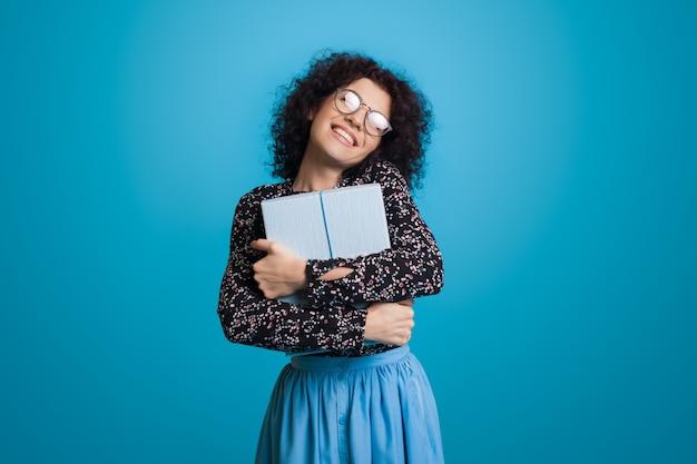 Dolce donna caucasica con capelli ricci e occhiali sta abbracciando una scatola presente sorridente su una parete blu dello studio in un vestito
