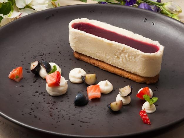 Cheesecake dolce con salsa di lamponi su un piatto scuro decorato con frutti di bosco