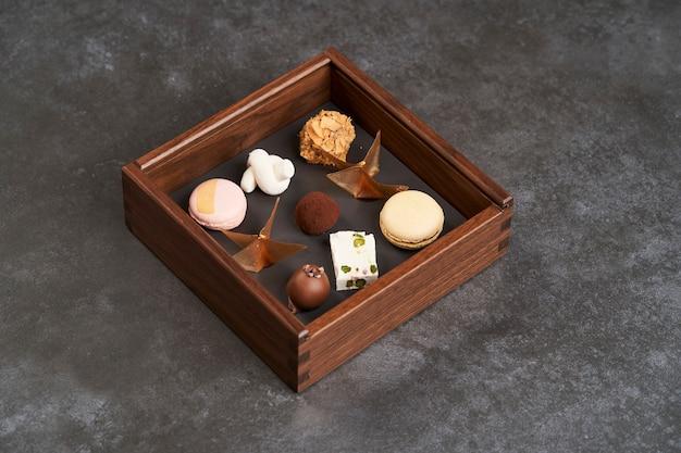 Caramelle di cioccolato zuccherato in scatola di legno, primo piano. un set di cioccolatini assortiti