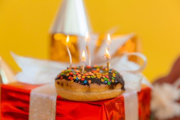 Ciambella al cioccolato dolce e candele accese su uno sfondo bokeh festivo. buon compleanno concetto.