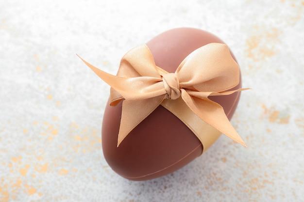 Uovo di pasqua di cioccolato dolce su marrone grigio