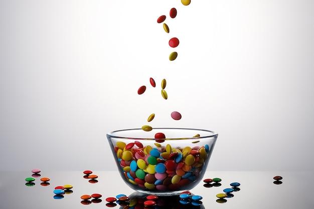 Dolce caramella colorata ricoperta di cioccolato che cade in una ciotola di vetro su sfondo bianco.