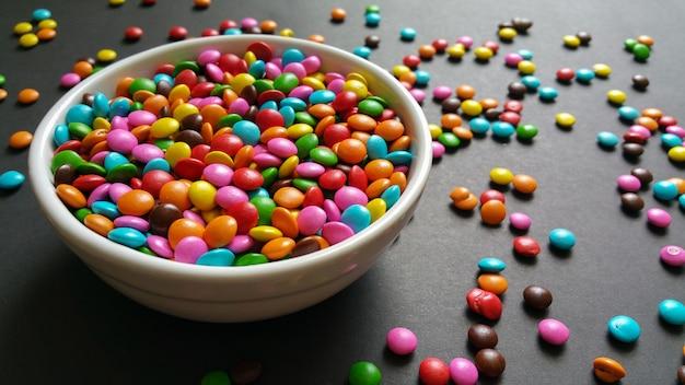 Coriandoli colorati dolci sparsi sulla tavola nera.