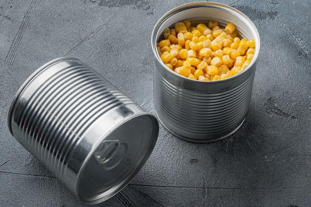 Chicchi di mais dolce in barattolo di latta, su sfondo grigio