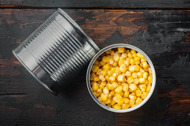 Grani di mais dolce in barattolo di latta, sul vecchio tavolo in legno scuro, vista dall'alto laici piatta
