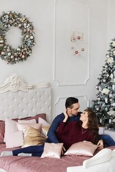 Coppia dolce abbracciati sul letto in camera da letto decorata per natale