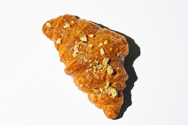 Croissant dolce con pasta di pistacchio e noci su un piatto bianco. luce forte