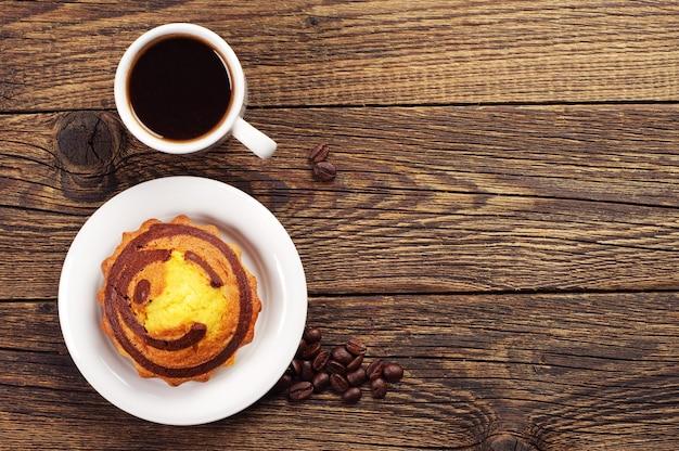 Bigné dolce con cioccolato e tazza di caffè sulla tavola di legno. vista dall'alto
