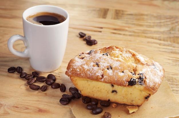 Cupcake dolce con uvetta e tazza di caffè sul vecchio tavolo di legno