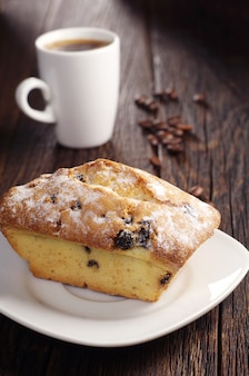 Cupcake dolce con uvetta e tazza di caffè caldo sul tavolo di legno scuro