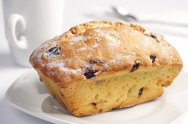 Bigné dolce con l'uva passa sul primo piano bianco del piatto