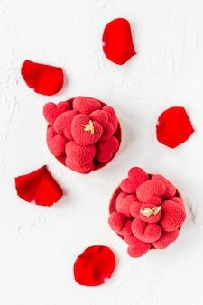 Tartelette di dessert dolce con cuori di mousse rossa in cima, decorata con petali di rose rosse, vista dall'alto