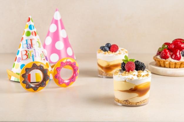 Dolci con frutti di bosco freschi e cappello di compleanno su sfondo luminoso.