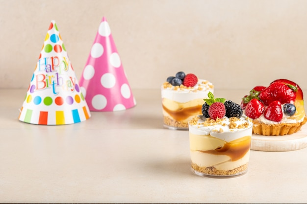 Dolci con frutti di bosco freschi e cappello di compleanno