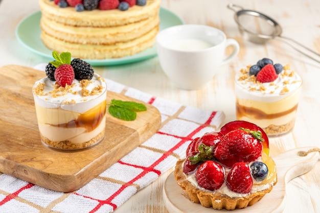 Dessert dolci con frutti di bosco freschi su fondo in legno.