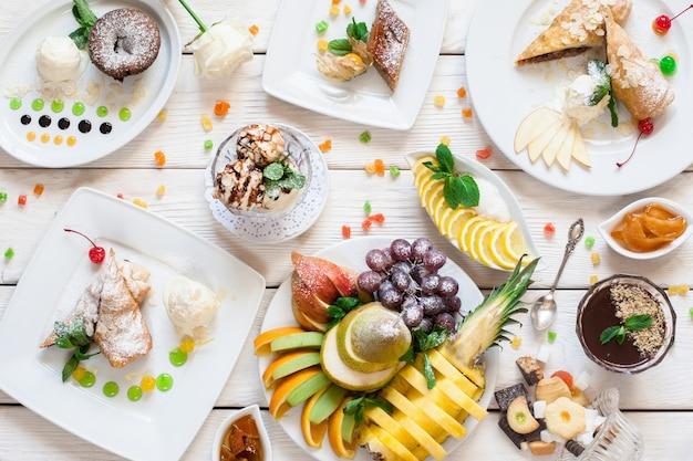 Dessert dolci con assortimento di frutta laici piatta. vista dall'alto su una varietà di torte, frutta fresca e dolci