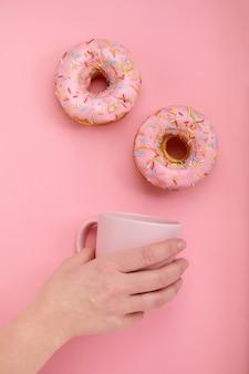 Ciambelle dolci su uno sfondo rosa la mano femminile tiene una tazza rosa con caffè. gioco di colori, concetto di colore, stilizzazione a un colore.
