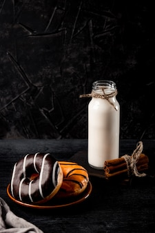Ciambelle dolci su un piatto e una bottiglia di latte