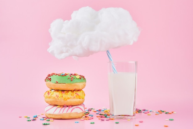 Ciambelle dolci con sprinkel e latte sotto una nuvoletta su sfondo rosa.