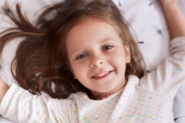 Concetto di sogni d'oro. la bambina affascinante che si trova a letto sul cuscino bianco nella sua camera da letto accogliente, prova ad addormentarsi, avendo espressione facciale felice