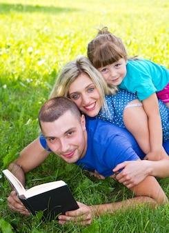 Dolce famiglia che legge un libro sull'erba verde Foto Premium